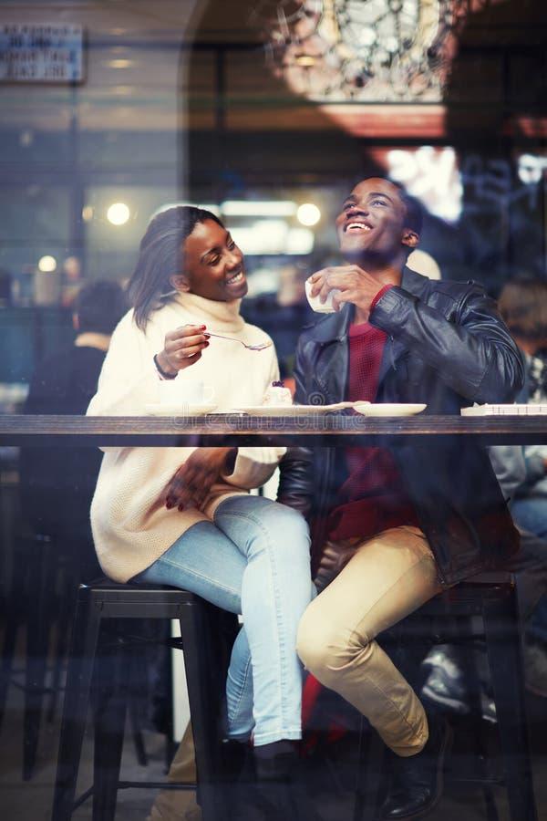 愉快的朋友喝咖啡一起,笑年轻夫妇在咖啡馆 库存图片