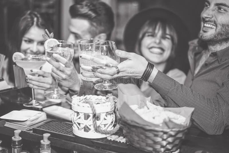 愉快的朋友欢呼与在葡萄酒酒吧的cockatil的-年轻人获得敬酒杯鸡尾酒的乐趣在客栈俱乐部 免版税库存图片