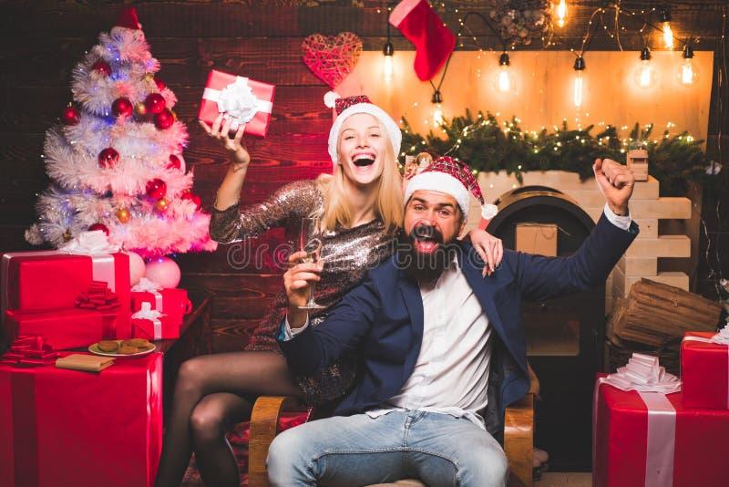 愉快的朋友的圣诞节打过工 醉了女孩庆祝新年 妇女和帅哥有圣诞老人礼服的 免版税库存图片