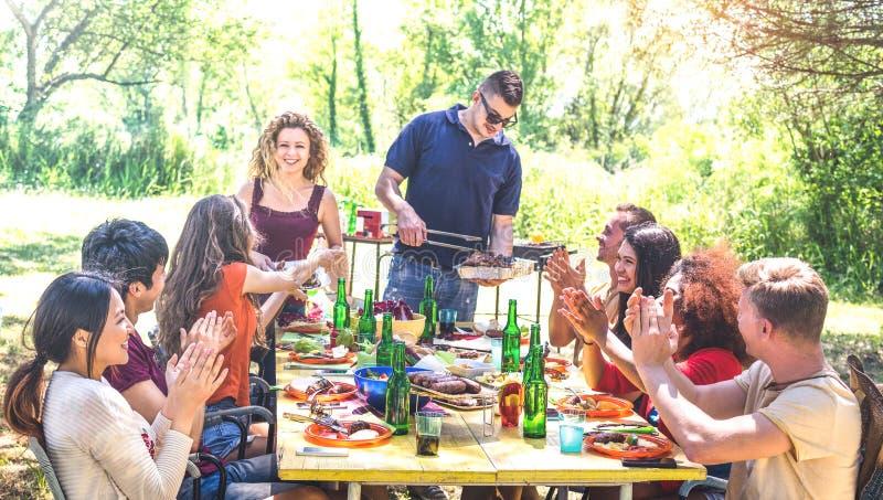 愉快的朋友获得乐趣一起在烤肉野餐党-年轻人在pic nic的millenials在露天节日 免版税库存图片