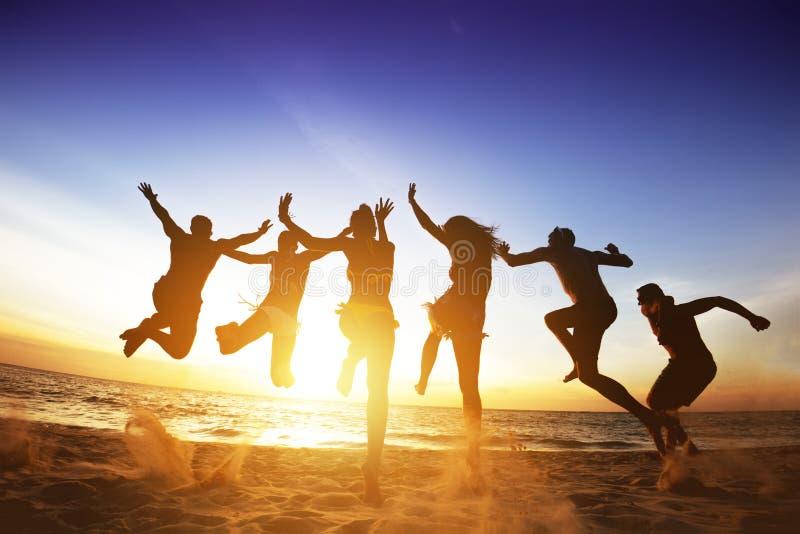 愉快的朋友跳海滩日落 友谊或队概念 免版税库存图片