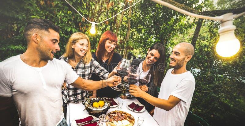 愉快的朋友饮用乐趣饮用的红酒在后院游园会-青年友谊概念一起在农厂房子葡萄园 免版税库存照片