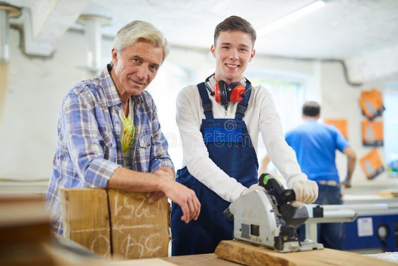 愉快的木匠和他的实习生在现代车间 免版税库存图片