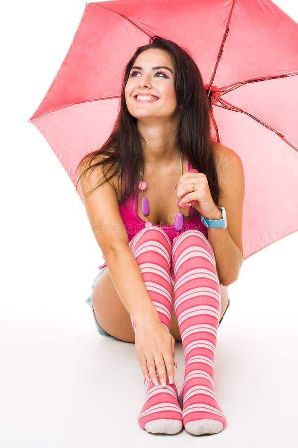 愉快的桃红色坐的伞妇女年轻人 免版税库存照片