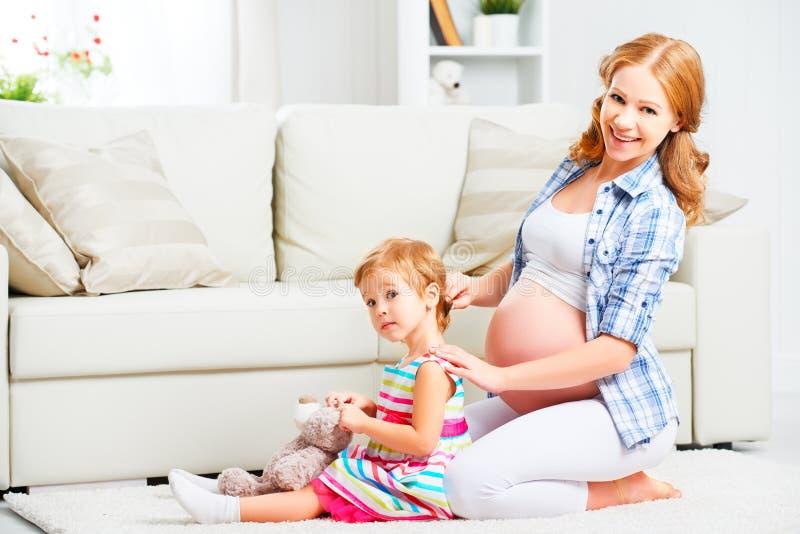 愉快的梳小女儿的头发的家庭怀孕的母亲 库存图片