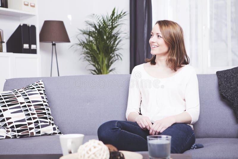 愉快的棕色毛发的女孩坐的微笑在沙发 库存照片