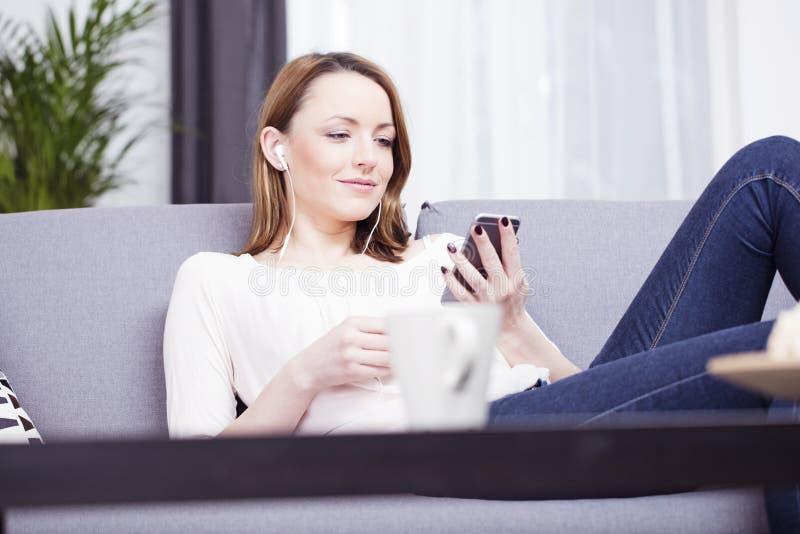 愉快的棕色毛发的女孩坐的微笑在沙发 库存图片