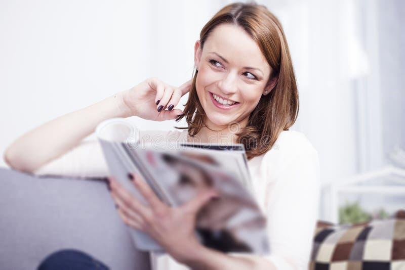 愉快的棕色毛发的女孩坐的微笑在沙发 免版税库存照片