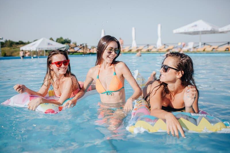 愉快的模型在游泳池 他们在照相机摆在 两个模型在浮游物在中部说谎并且看妇女 她 库存照片