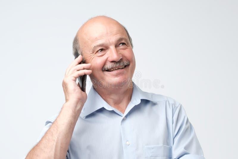 愉快的欧洲老人画象谈话在电话和微笑 免版税库存图片