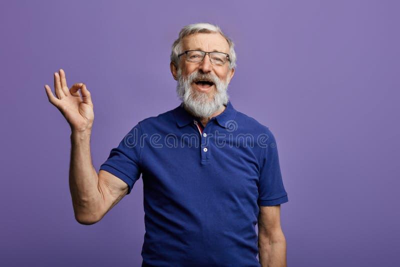 愉快的正面英俊的老人显示Ok标志,没有问题,健康是好的 库存图片