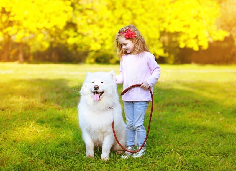愉快的正面获得小女孩和的狗乐趣 免版税库存照片