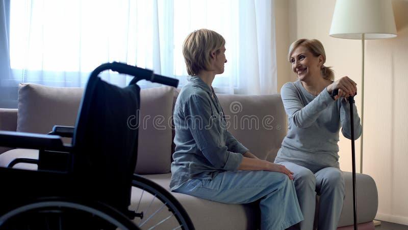 愉快的残疾母亲谈话与中间年迈的女儿,家族关系 免版税图库摄影