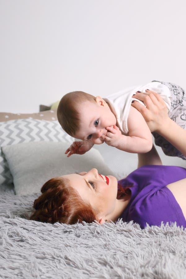 愉快的母亲使用与她的在床上的小婴孩 库存图片