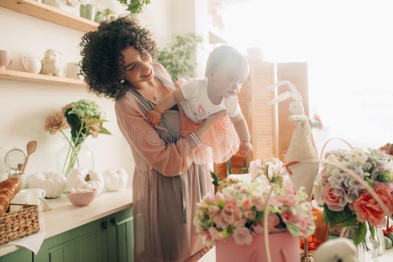 愉快的母亲使用与她的婴孩在厨房里 免版税库存图片