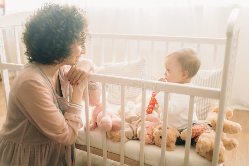 愉快的母亲其次坐她的小儿床的婴孩 免版税库存图片