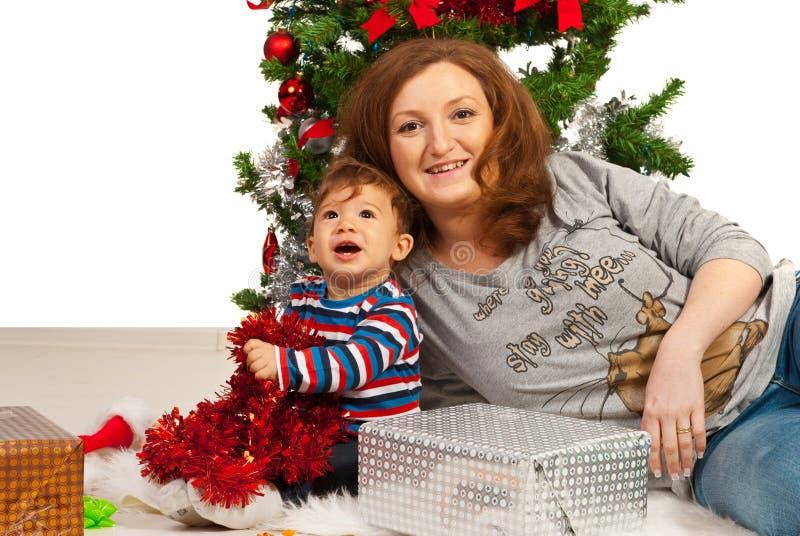 愉快的母亲和儿子在Xmas树下 免版税库存照片