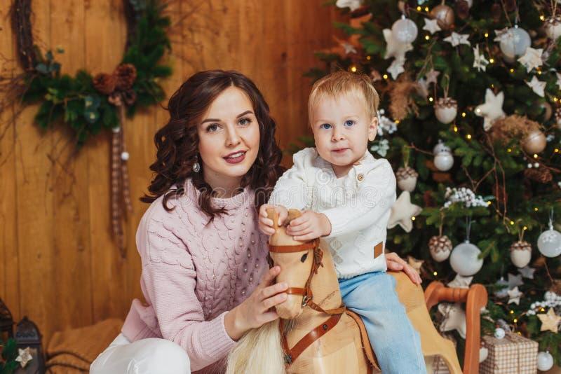 愉快的母亲和儿子男婴画象  圣诞节装饰生态学木 免版税库存照片