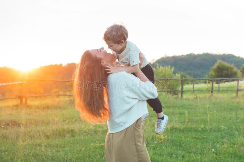 愉快的母亲和儿子自然的在日落 家庭、孩子和愉快的人概念 图库摄影