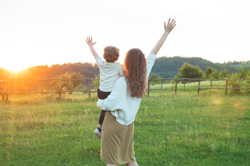愉快的母亲和儿子自然的在日落 家庭、孩子和愉快的人概念 库存照片