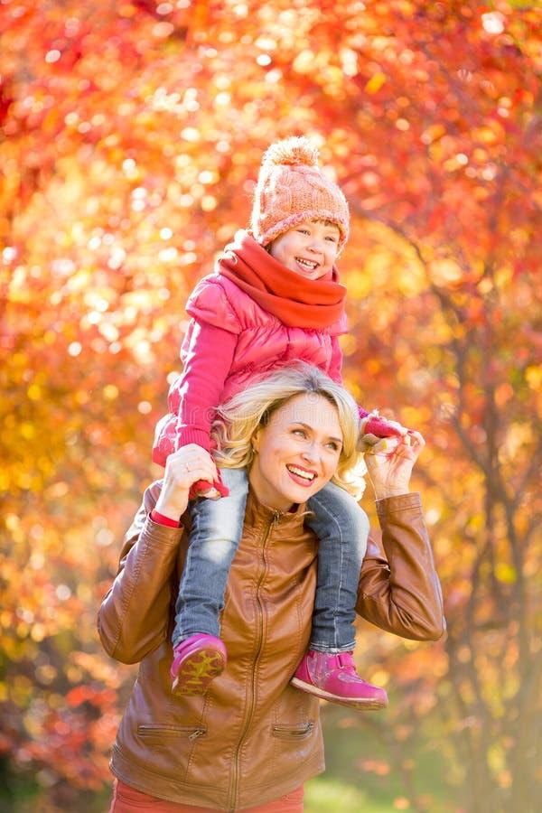 愉快的母亲和和微笑的孩子一起室外在秋天 库存照片