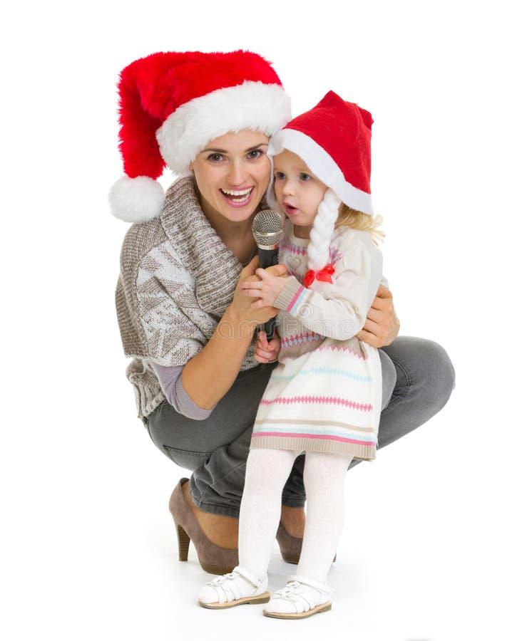 愉快的母亲和唱歌到话筒的女婴 免版税库存照片