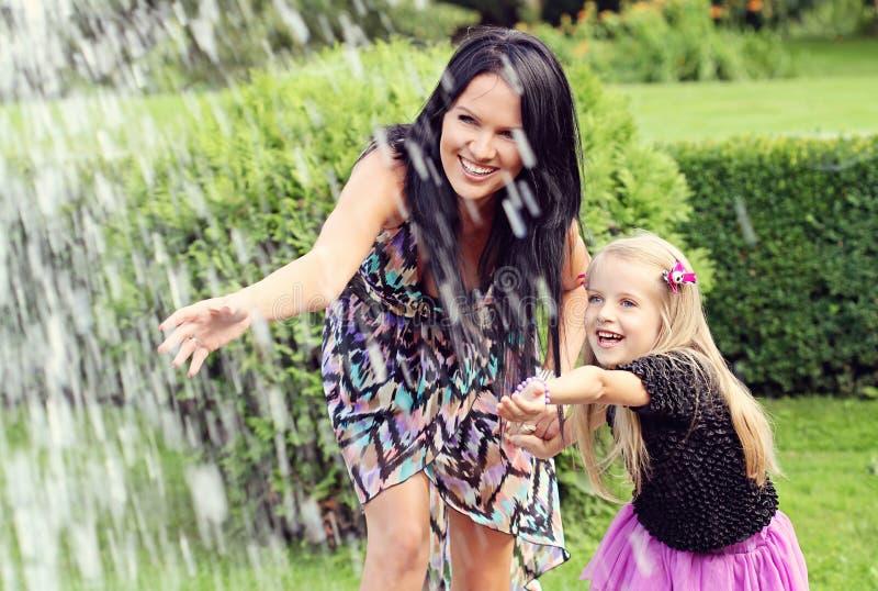 愉快的母亲和女儿在公园 库存图片