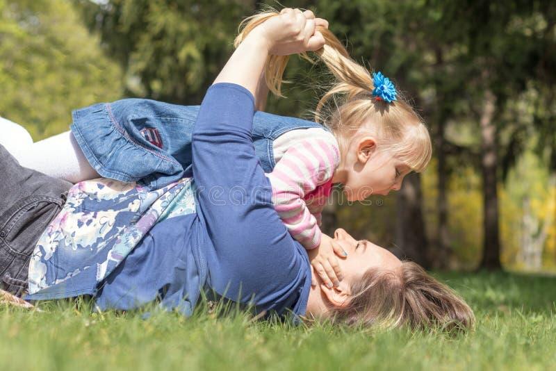 愉快的母亲和女儿在春天公园 库存图片