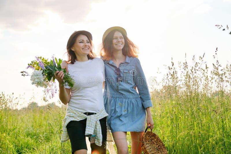 愉快的母亲和女儿夏天画象自然的在草甸 免版税库存图片