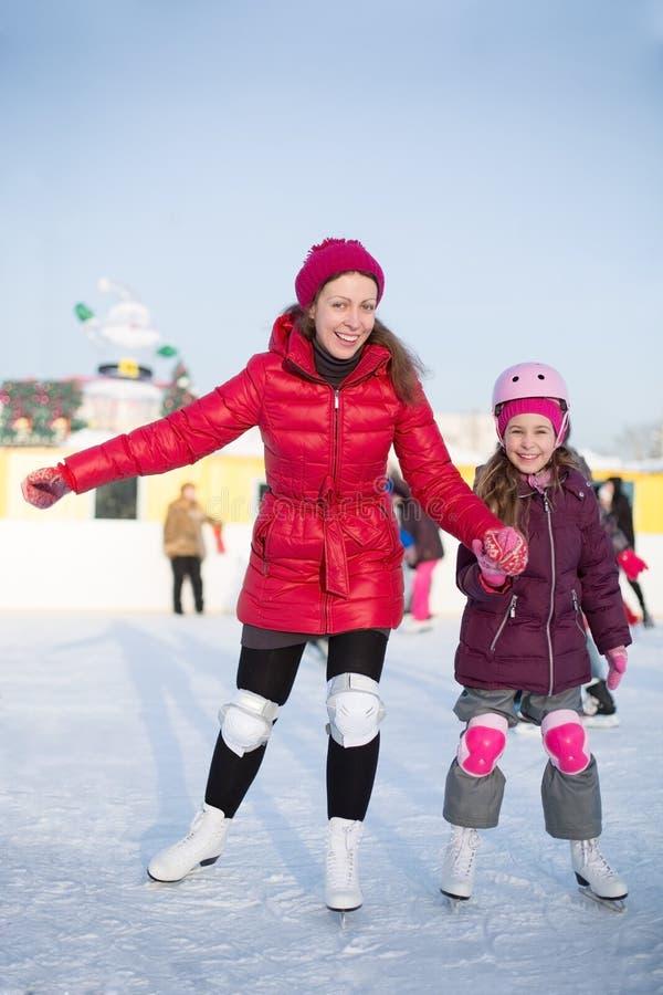 愉快的母亲和女儿是滑冰的atoutdoor滑冰场 库存照片