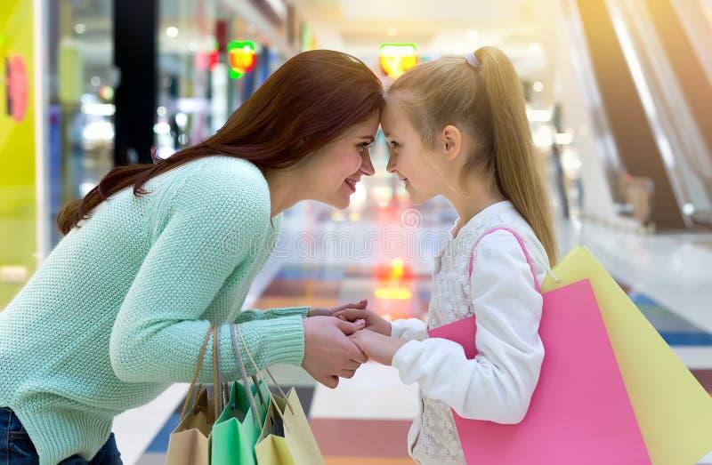 愉快的母亲和女儿有购物带来的 与家庭的购物的时间 免版税库存图片