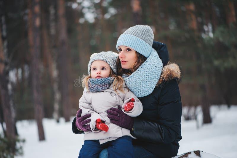 愉快的母亲和女儿步行的在多雪的冬天 库存照片