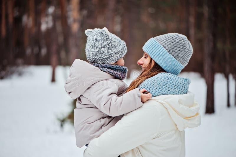 愉快的母亲和女儿步行的在多雪的冬天 免版税库存图片