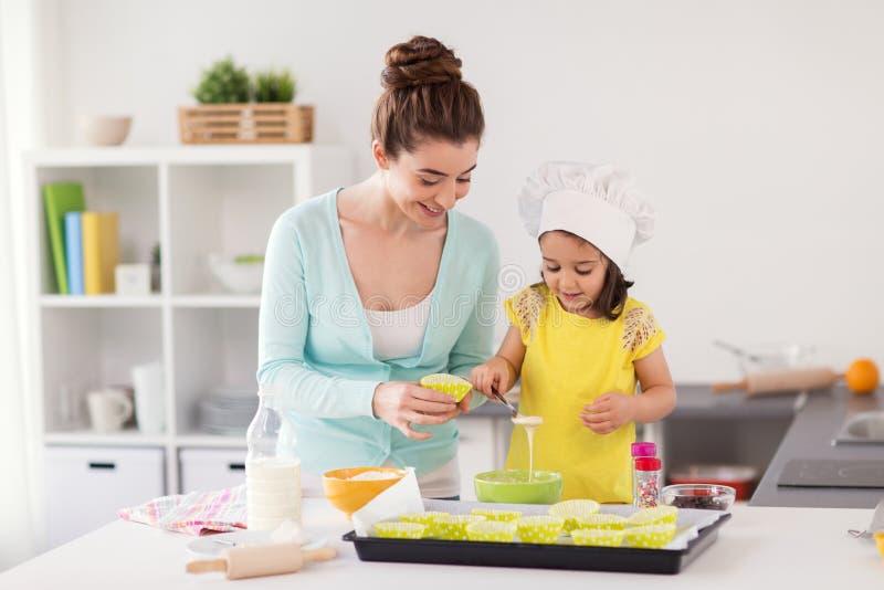 愉快的母亲和女儿烘烤杯形蛋糕在家 库存照片