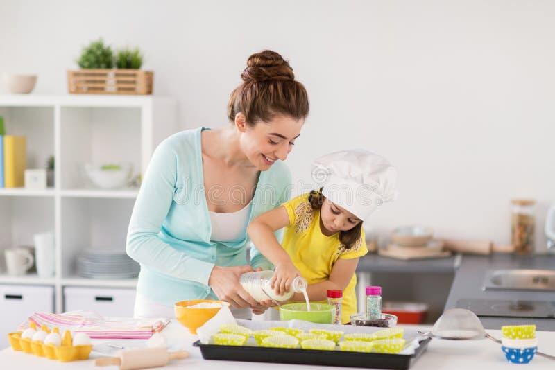 愉快的母亲和女儿烘烤杯形蛋糕在家 免版税图库摄影