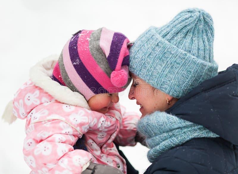 愉快的母亲和女儿画象在冬天 库存照片