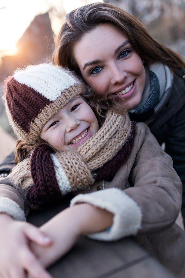 愉快的母亲和女儿获得乐趣在街道 免版税库存图片