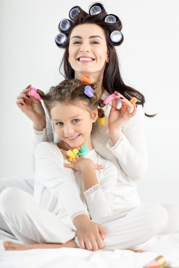 愉快的母亲和女儿获得的卷发的人的乐趣一起 免版税库存图片