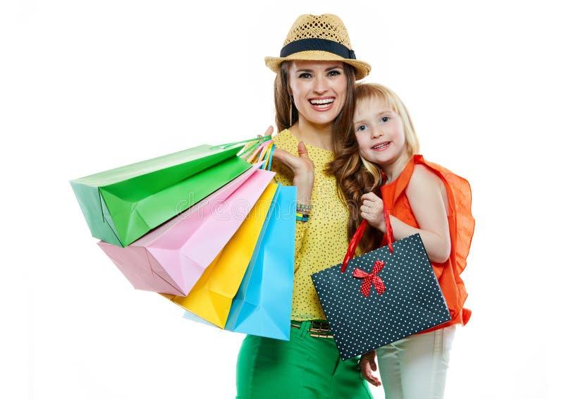 愉快的母亲和女儿画象有购物袋的 免版税库存照片