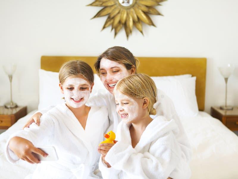 愉快的母亲和女孩浴巾的在床上 免版税库存照片