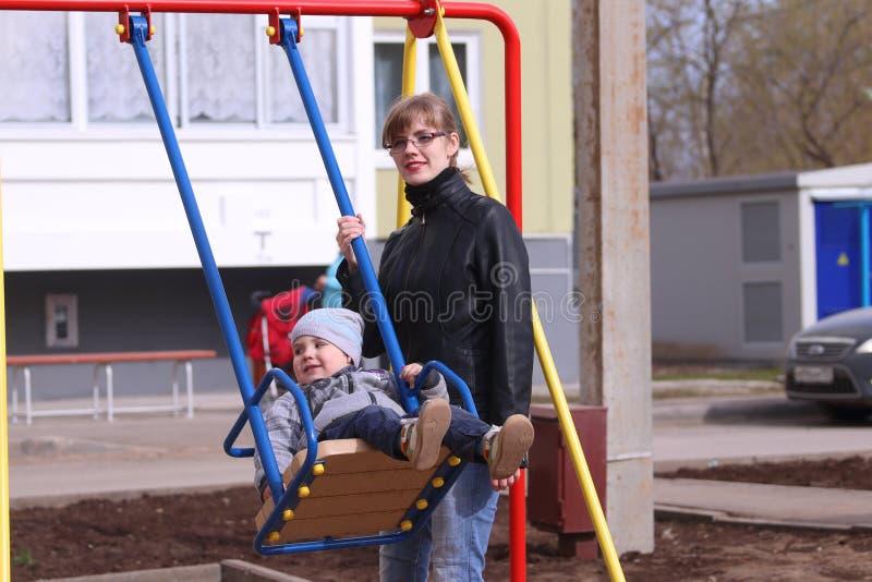 愉快的母亲和她的一点儿子摇摆 图库摄影