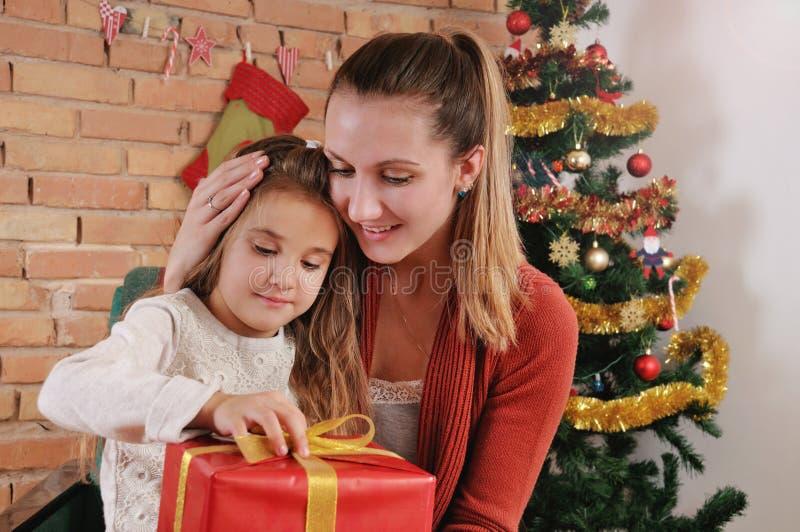 愉快的母亲和她的婴孩画象在圣诞树附近 图库摄影