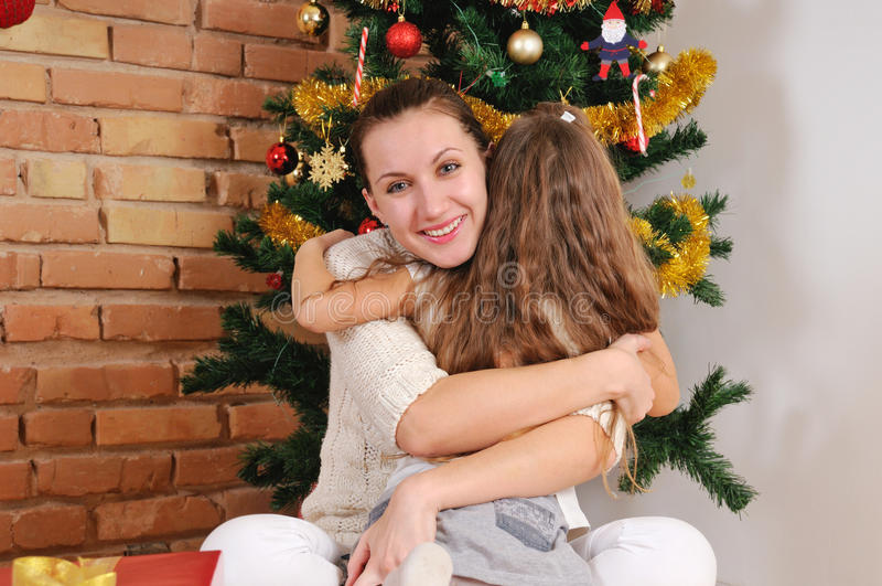 愉快的母亲和她的婴孩Embracie在圣诞树附近 免版税库存图片