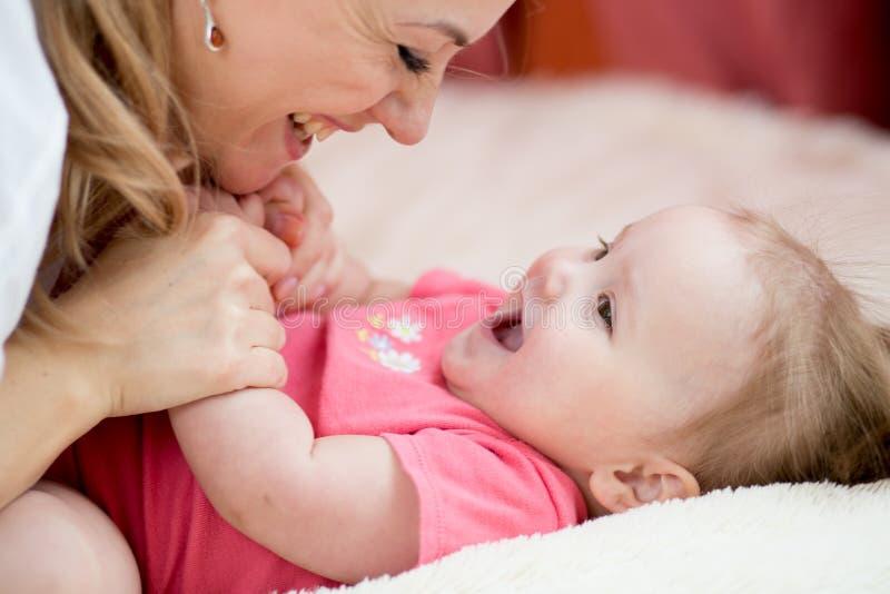 愉快的母亲和婴孩在家有乐趣消遣 免版税库存图片