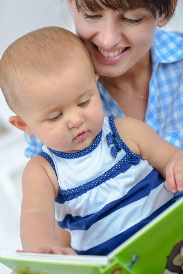 愉快的母亲和婴孩阅读书 免版税库存照片