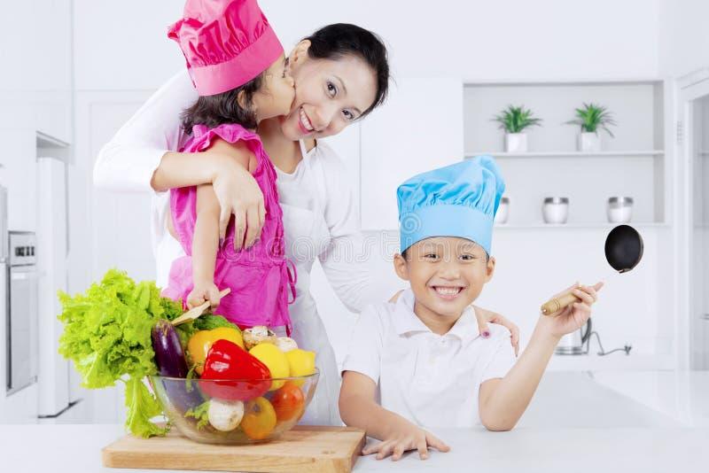愉快的母亲和孩子与菜 免版税库存照片
