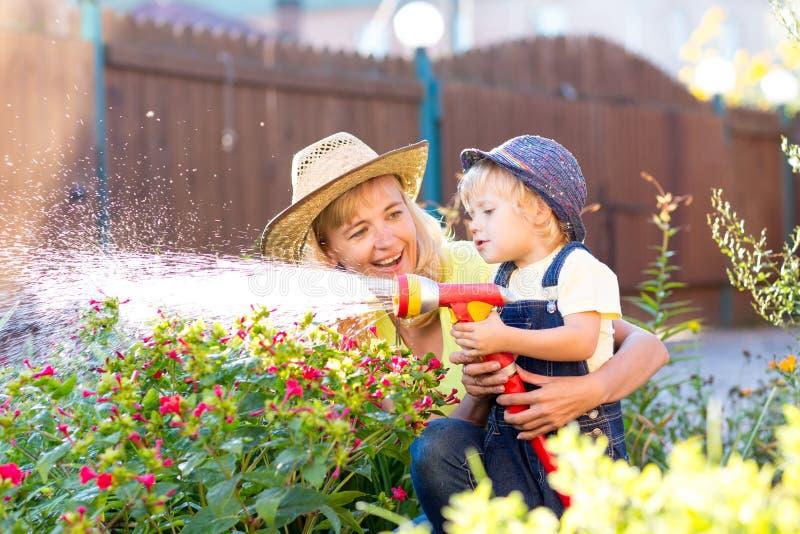 愉快的母亲和孩子在国内庭院里浇灌 库存照片