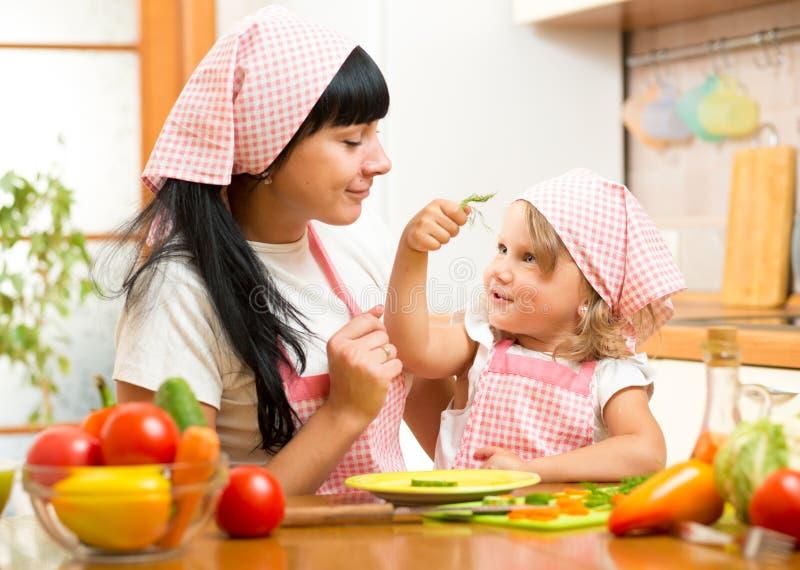 愉快的母亲和孩子女儿用沙拉n厨房 免版税库存照片
