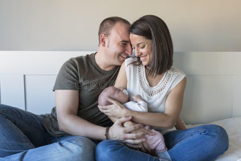 愉快的母亲和父亲有她的女婴的在家 户内生活方式和家庭爱概念 免版税库存图片