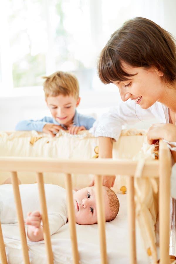 愉快的母亲和男孩轻便小床的 免版税图库摄影